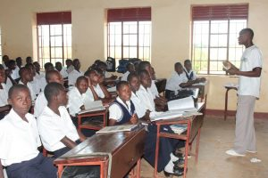 A group of Ugandan students all wearing a school uniform of white shirts and navy trousers sat at wooden desks watching their teacher at the front of the class. Many of the students are looking at the camera.