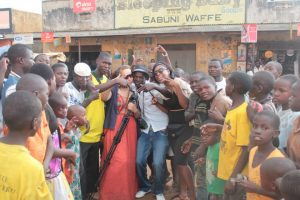 A group of Ugandan young people and Christina pulling faces and waving their arms towards the camera