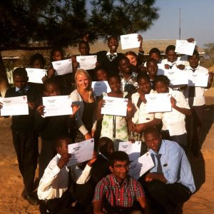 A group of Zambian students all holding a white certificate proudly and smiling at the camera outside in Zambia