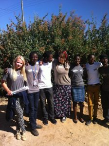 A group of UK and Ugandan volunteers and activists stood together in front of a tree facing the camera