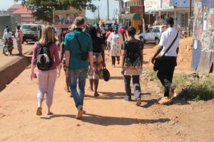 Walking down a populated street in Uganda, a group of Ugandan and UK volunteers with their backs to the camera