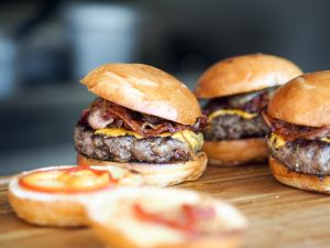 three bacon cheeseburgers on a wooden board