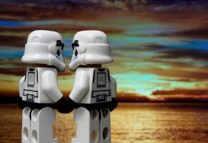 Two stormtrooper lego figures holding hands stood in front of a sunset over water