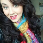 A photo of Christina Berry-Moorcroft. She is a white woman with dark, curly hair. She is wearing a brightly coloured scarf and bright pink lipstick.