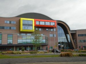 A photo of Alder Hey Children's Hospital - the hospital was recently redesigned and rebuilt using ideas from children. Two of the blocks of windows are surrounded by coloured tiling and the roof is curved and sloped.