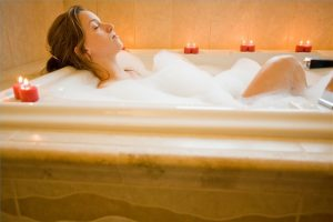 A woman relaxing in a bubble bath surrounded by lit candles