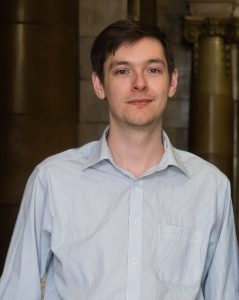 Michael Marshall wearing a pale blue shirt. Marsh is tall, slim, white, cis, male and has brown hair.